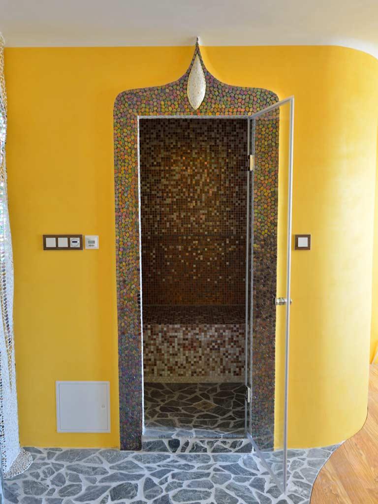 Dampfbad: Lehmputz (Wand) mit durch Glasmosaik betontem Eingang