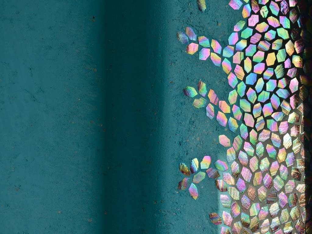 Mosaikkunst: Regenbogenfarben spiegeln die Sonne im angeleuchteten Mosaik wieder